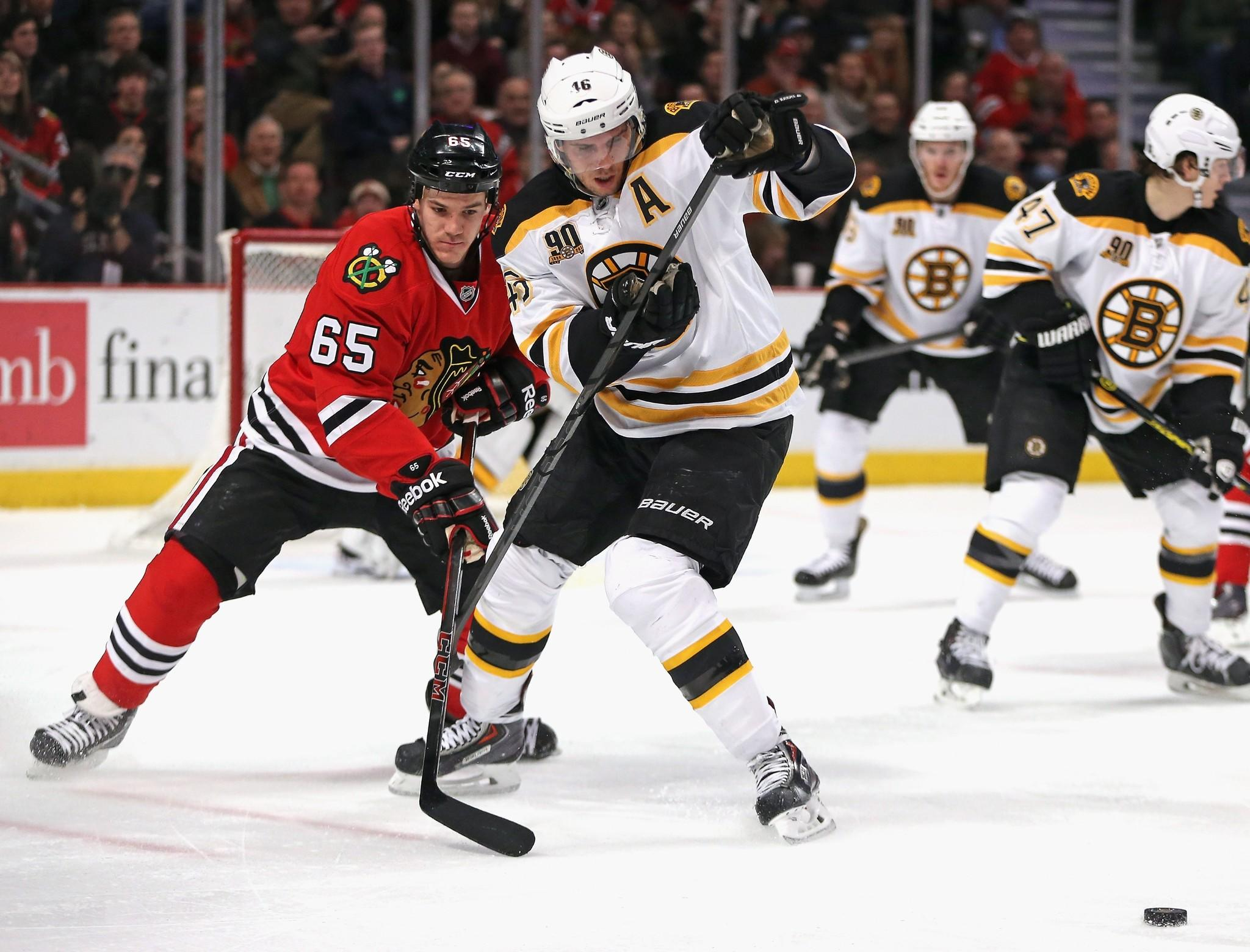 Andrew Shaw #65 of the Chicago Blackhawks and David Krejci #46 of the Boston Bruins moves to the puck at the United Center on January 19, 2014 in Chicago, Illinois.