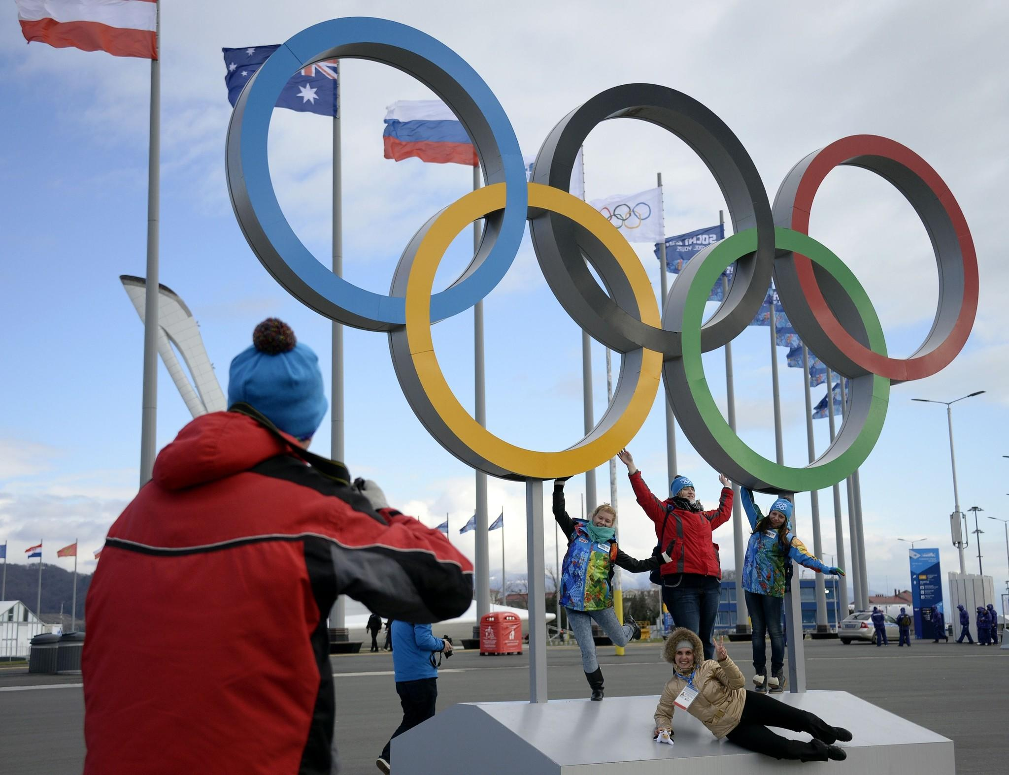 Volunteers pose in front of the Olympic rings prior to the start of the 2014 Sochi Winter Olympics on February 1, 2014 in Sochi.