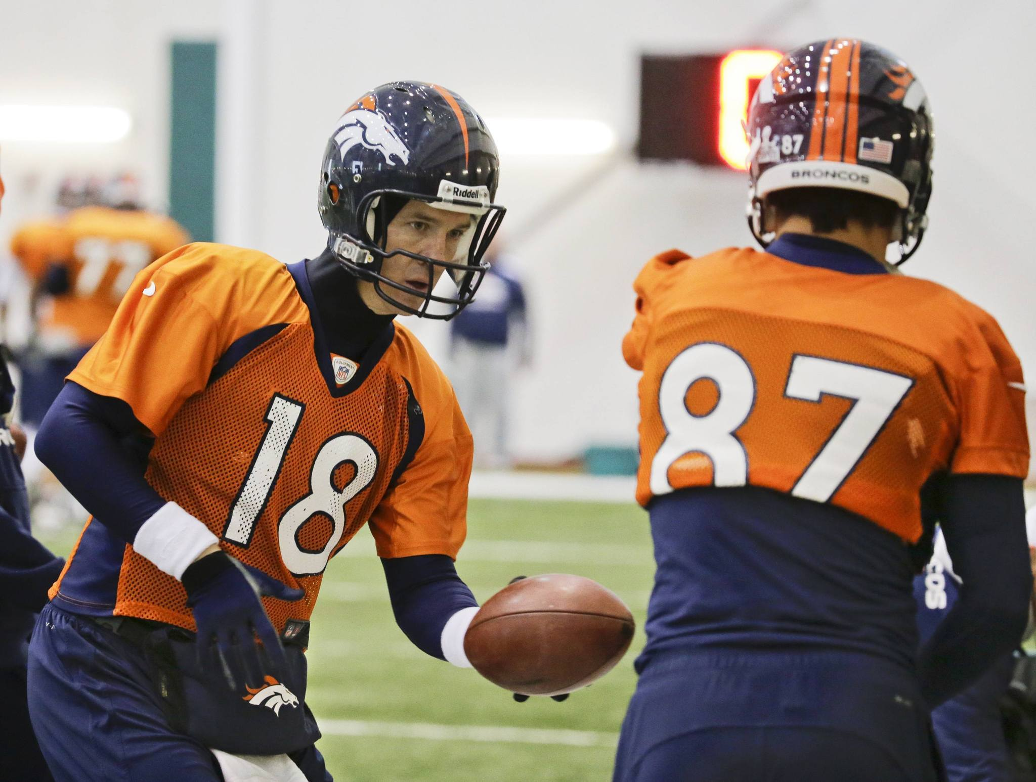 Denver Broncos quarterback Peyton Manning (L) practices handing off the ball with wide receiver Eric Decker during their practice session for the Super Bowl at the New York Jets Training Center in Florham Park, New Jersey, January 31, 2014.
