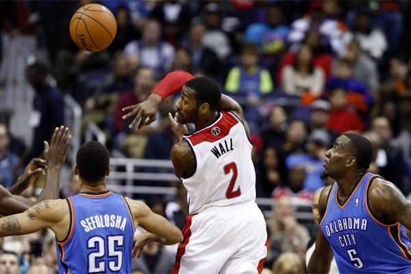 Washington guard John Wall passes the ball over his shoulder past Oklahoma City guard Thabo Sefolosha and center Kendrick Perkins.