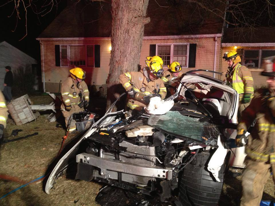 Firefighters work to remove passengers after a car struck a tree on Hillside Drive in South Windsor early Sunday.