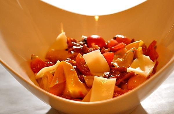 <i>Pappardelle</i> noodles are served with prosciutto and cherry tomatoes.