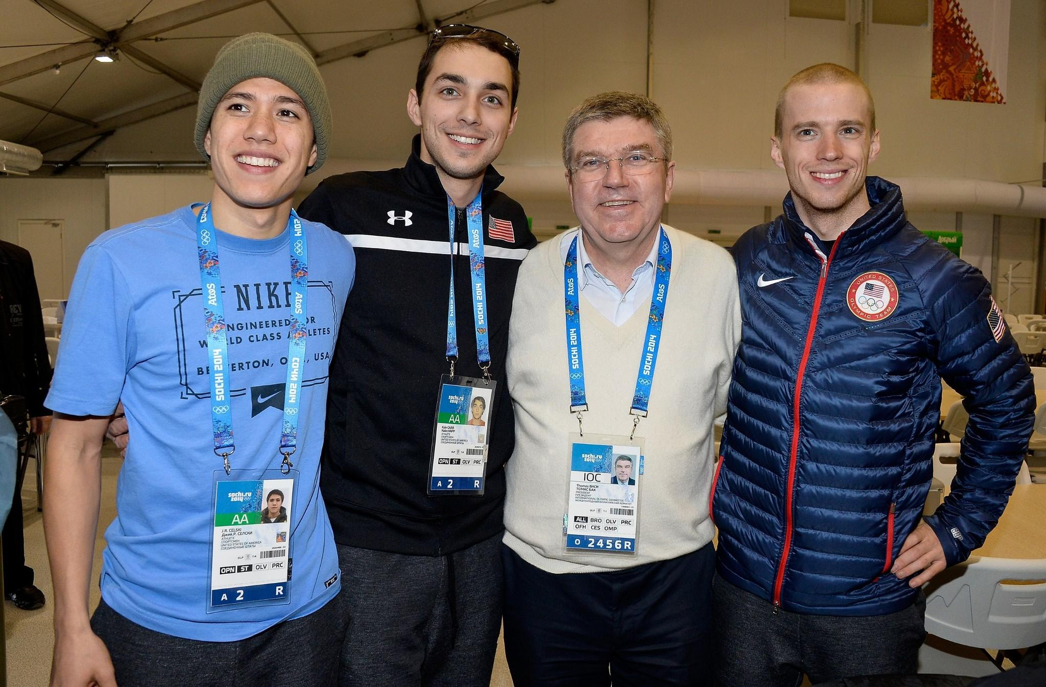 International Olympic Committee President Thomas Bach (white shirt) poses with U.S. speed skaters (L-to-R) J.R. Celski, Kyle Carr and Patrick Meek at the coastal Olympic Village in Sochi.