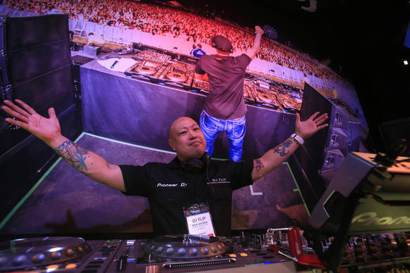 DJ Flip (aka Rick Sajorda) rocks the Pioneer booth at the NAMM Show at the Anaheim Convention Center last month.