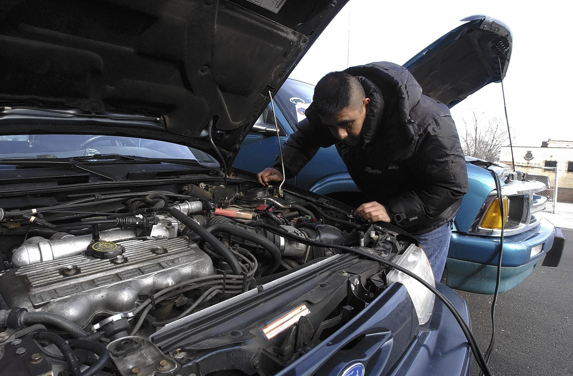 Dominguez, working in cold temperatures, attaches jumper cables to the batteries of his SUV at right and the car of a friend at left but has no luck getting the car started.