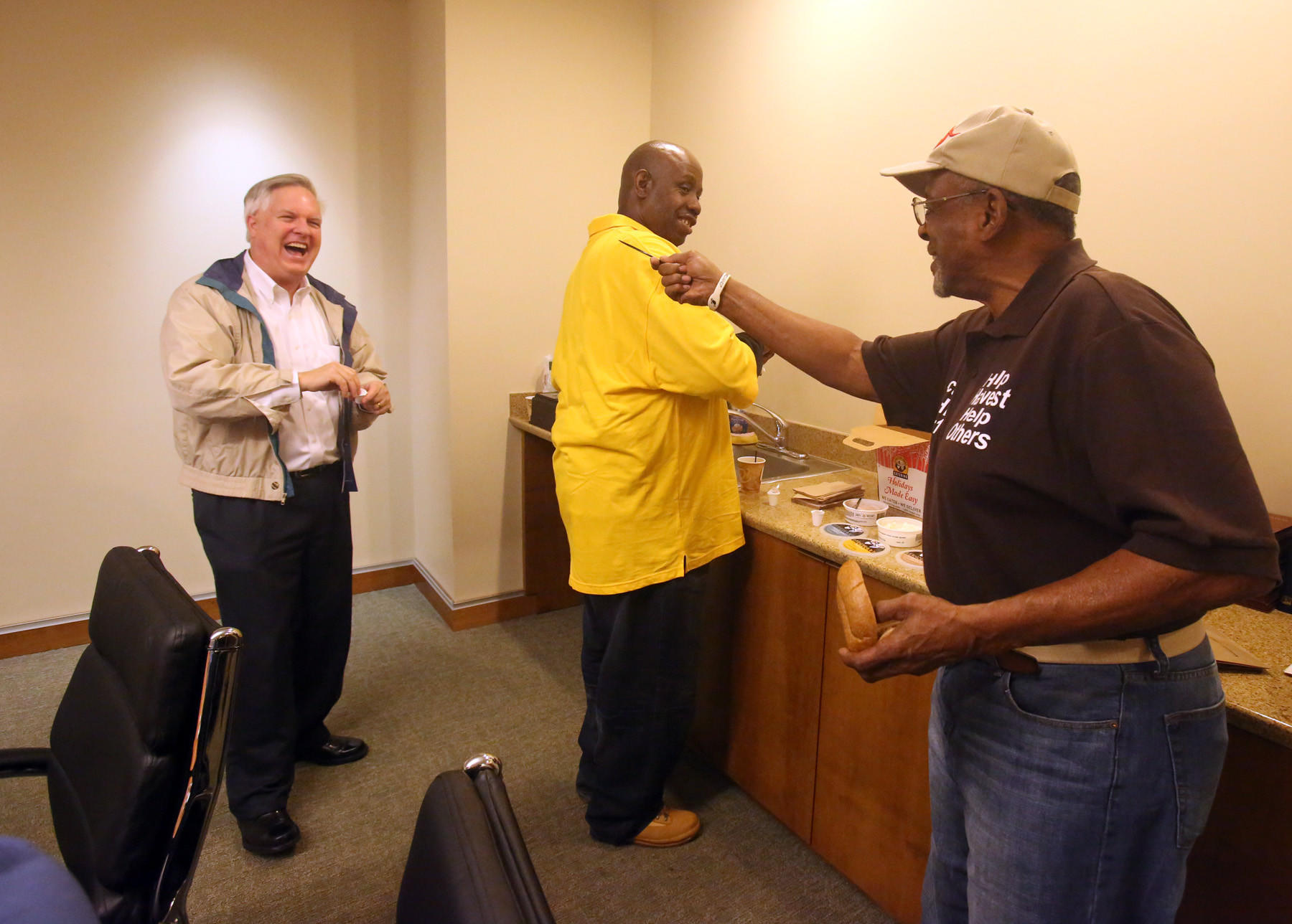 Leo Lorenz, left, member First United Methodist Church, Carl Battle, of Harvest Baptist Church, center, and Robert Woodyard, Harvest Baptist Church, have a conversation Wednesday, January 29, 2014 as they have some bagels and coffee at First United Methodist Church in downtown Orlando.