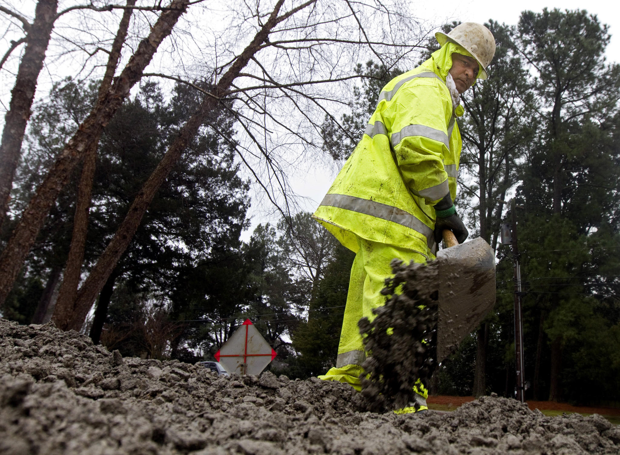 Rubin Aguon, a senior pipe layer with Newport News Waterworks, covers a repaired water pipe with gravel as crews worked in damp conditions on Monday morning in Hilton Village.