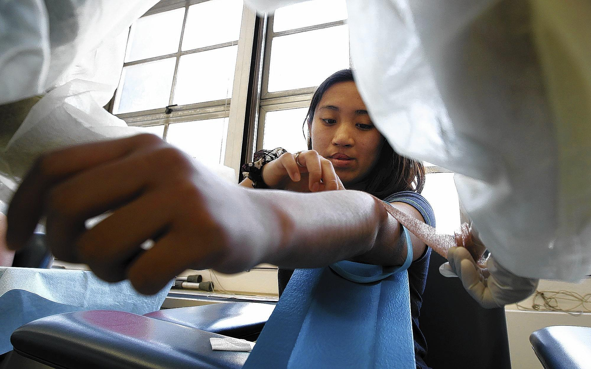 Student Lourdes Valderama, 20, center, gets bandaged up after having her blood drawn in a phlebotomy course at Long Beach City College, which is involved in a pilot program offering extra sessions of high-demand courses at a higher price than regular classes.