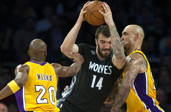 Timberwolves center Nikola Pekovic tries to power his way to the basket against Lakers guard Jodie Meeks center Robert Sacre during a game earlier this season at Staples Center.
