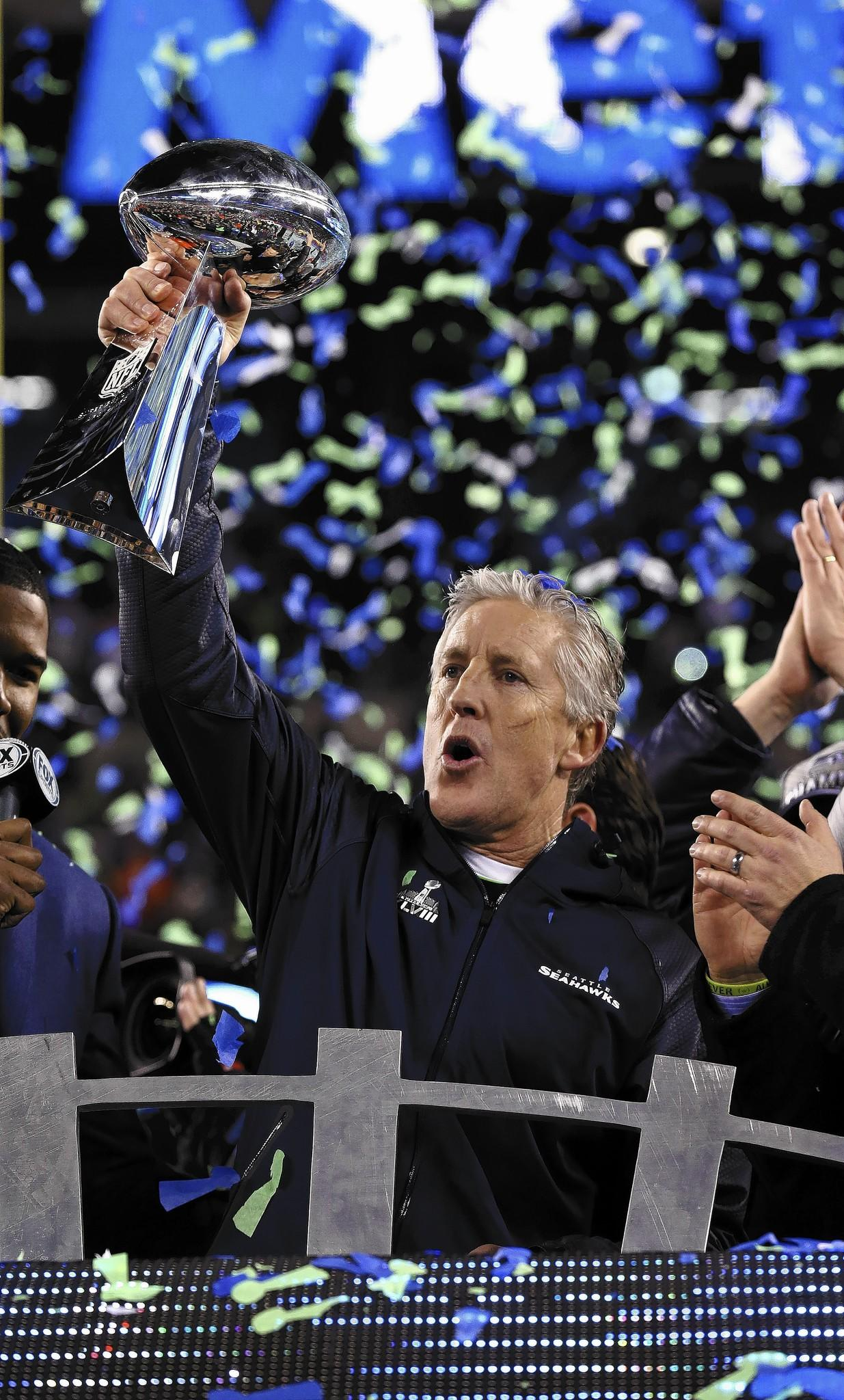 Seahawks coach Pete Carroll hoists tthe Vince Lombardi Trophy on Sunday night.
