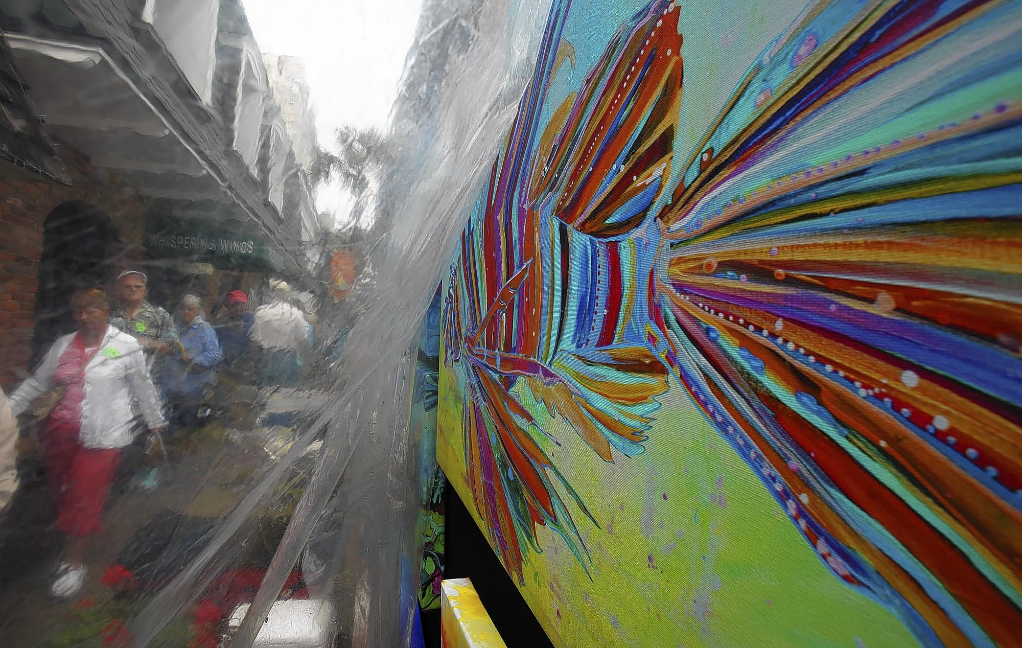 A fish painting is covered with plastic to protect it from the rain at Jen Callahan's booth during the Mount Dora Arts Festival in downtown Mount Dora on Saturday, February 1, 2014. Callahan is from Virginia. (Stephen M. Dowell/Orlando Sentinel)