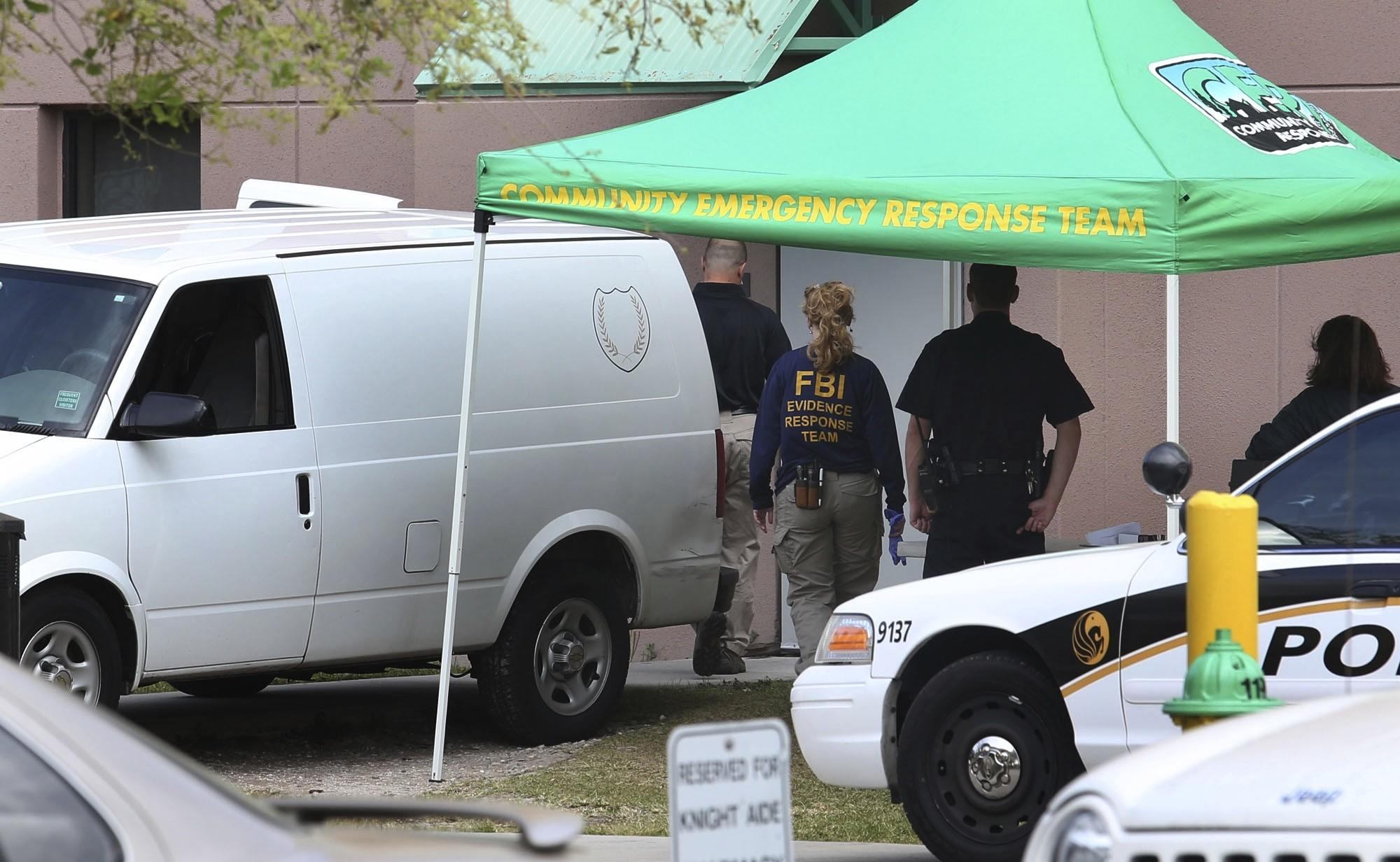 The medical examiner van is parked outside the dorm building as FBi evidence response team arrives Monday, March 18, 2013 to UCF after a student was found dead on campus. Explosives and guns were found in a dorm building,background, where she was evacuated from little after midnight. (Red Huber / Orlando Sentinel)