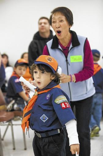 Yasuko Fordiani gives encouragement to Nathan Gonzalez, 6, during a game of Wii bowling at the Rodgers Seniors' Center. Seniors from the center played Wii bowling with Cub Scouts from Pack 435 in Huntington Beach.