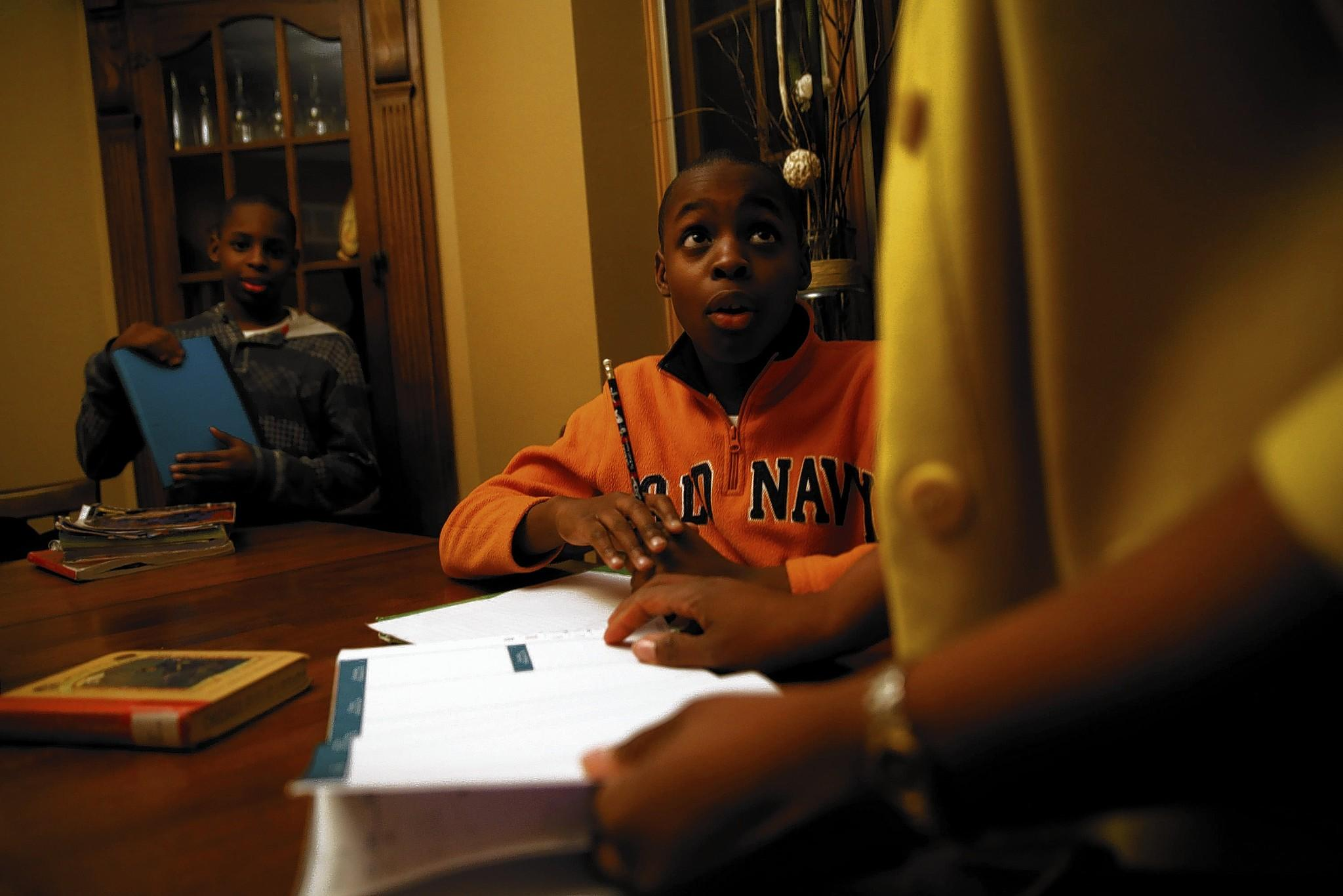Sixth-grade twin brothers Bryce, right, and Brandon Jenkins get homework help Monday from their mother, Cherya, who is concerned that Chicago Public School students taking the new assessment test for selective-enrollment high schools will be at a disadvantage against private school students taking the same test as in previous years.