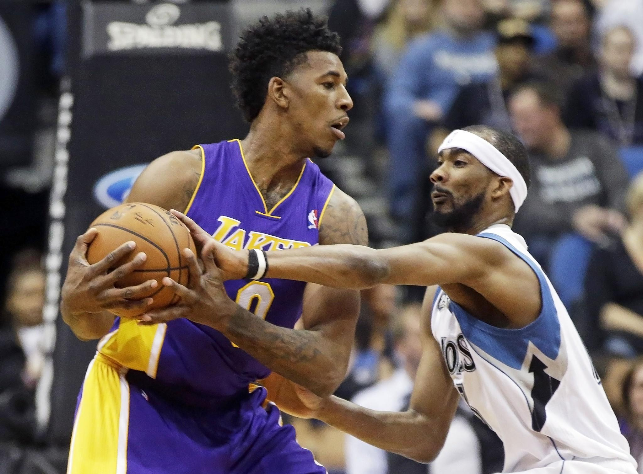 Nick Young tries to keep the ball away from Minnesota's Corey Brewer during the first quarter Tuesday at the Target Center in Minneapolis. Young went down with a knee injury against Cleveland on Wednesday.