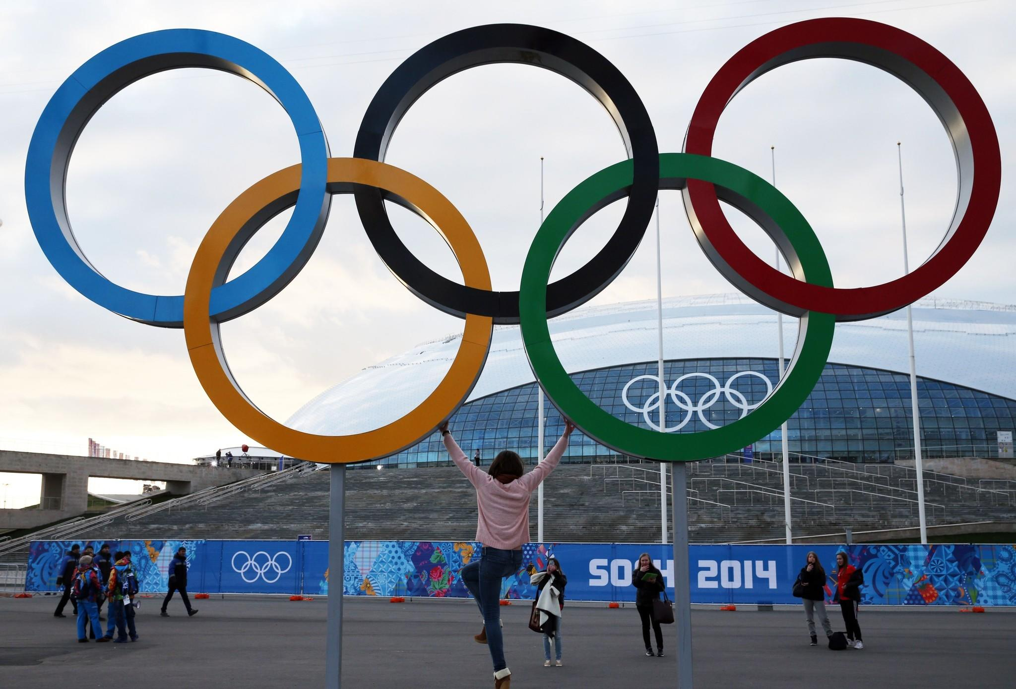 Visitors take pictures with the Olympic rings outside the Bolshoy Ice Dome, where some ice hockey games will take place, prior to the start of the 2014 Sochi WInter Olympics.