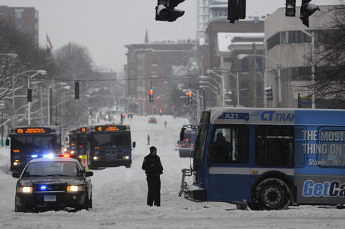 Hartford police stand by directing traffic around a stuck bus blocking south bound Main Street in Hartford.