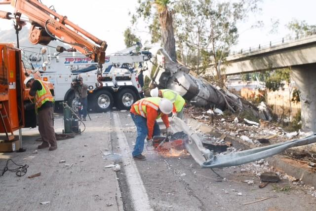 Crews work to remove debris from an overturned tanker carrying milk on the southbound Glendale (2) Freeway in Glendale.
