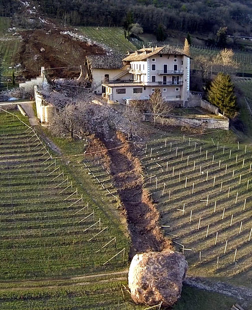 In this photo taken Jan. 23, a huge boulder is seen after it missed a farm house by a couple of feet but destroyed a barn and finally stopped in a vineyard. A second giant boulder, which detached during the same landslide on Jan. 21, stopped next to the house in Ronchi di Termeno, in northern Italy. According to reports, the Trebo family living there was unharmed in the landslide.