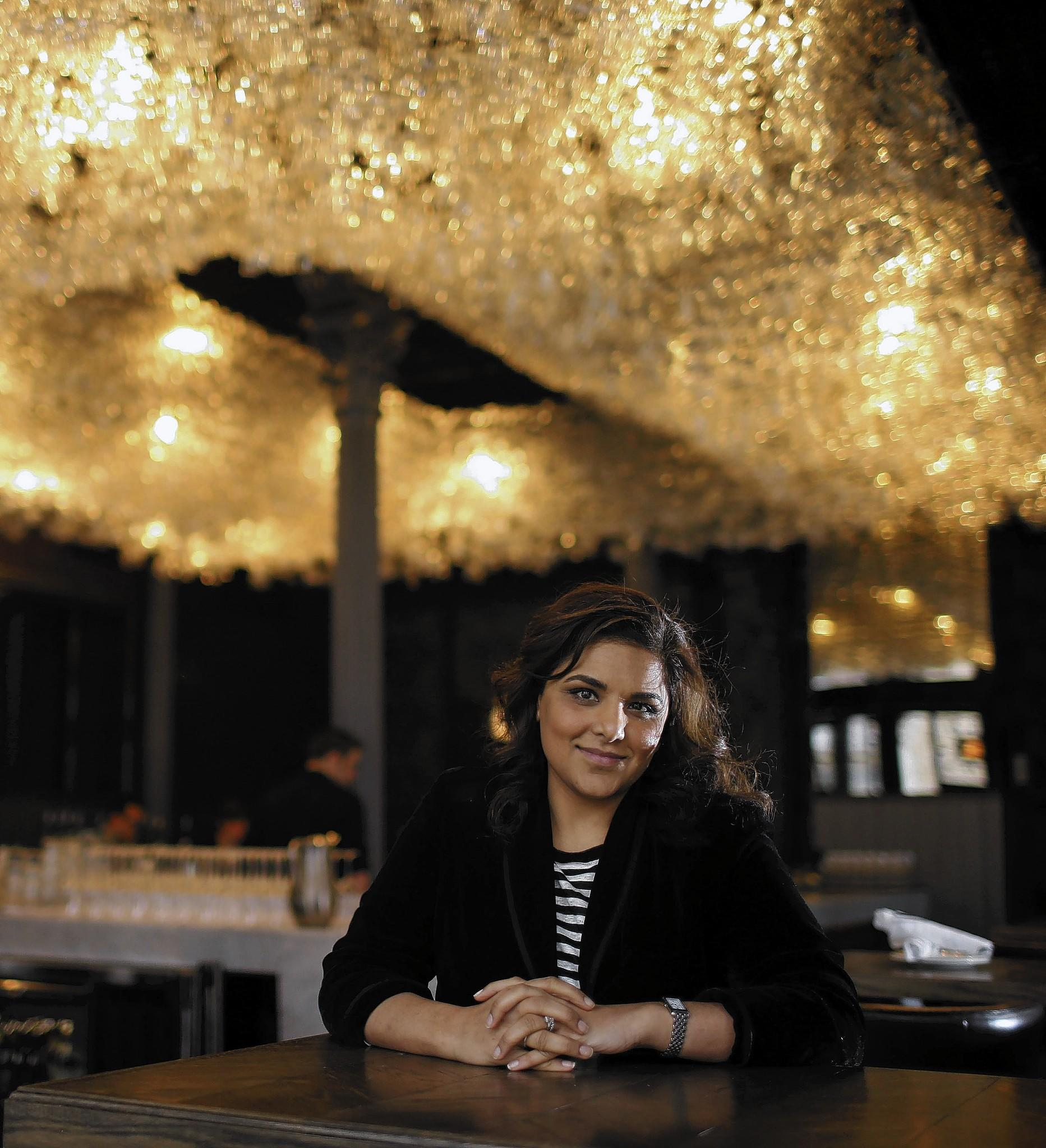 Alpana Singh in the front bar with a wine glass chandelier at Boarding House .