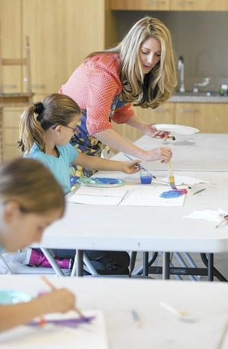 Rebecca Faubion, the owner of Artful Everyday, helps Nicole Anderson and her children William, 3, and Barrett, 1, paint with cars at the Laguna Beach Community and Susi Q Center on Feb. 1.