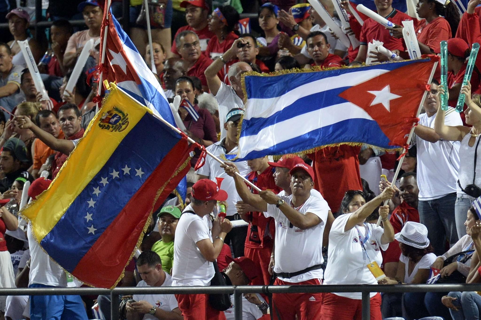 Supporters of Venezuela's Navegantes del Magallanes and Cuba's Azucareros de Villa Clara wave flags during their 2014 Caribbean baseball series game, in Porlamar, Margarita Island, Nueva Esparta state, Venezuela on February 2, 2014.