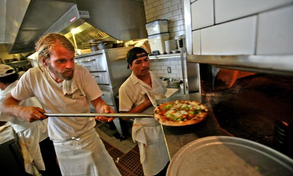 Gjelina chef Travis Lett pulls a pizza from the oven.