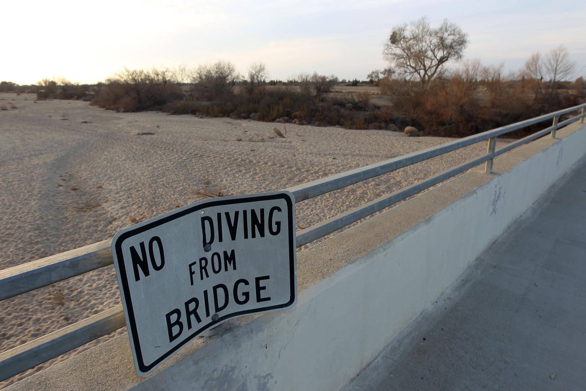 A sign from wetter times warns people not to dive from a bridge over the Kern River, which has been dried up by water diversion projects and a shortage of rain, in Bakersfield.