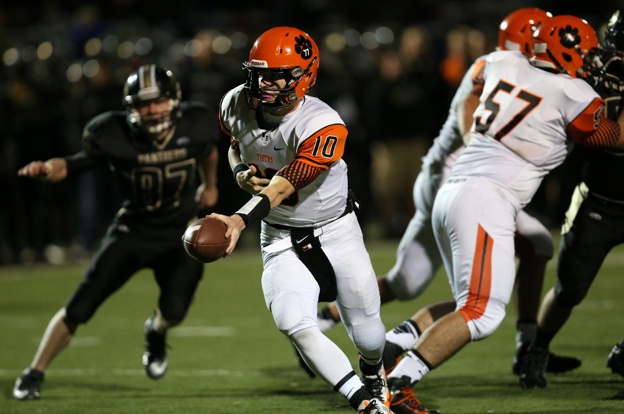 Wheaton Warrenville South quarterback Ryan Graham hands the ball off in the first half against Glenbard North.