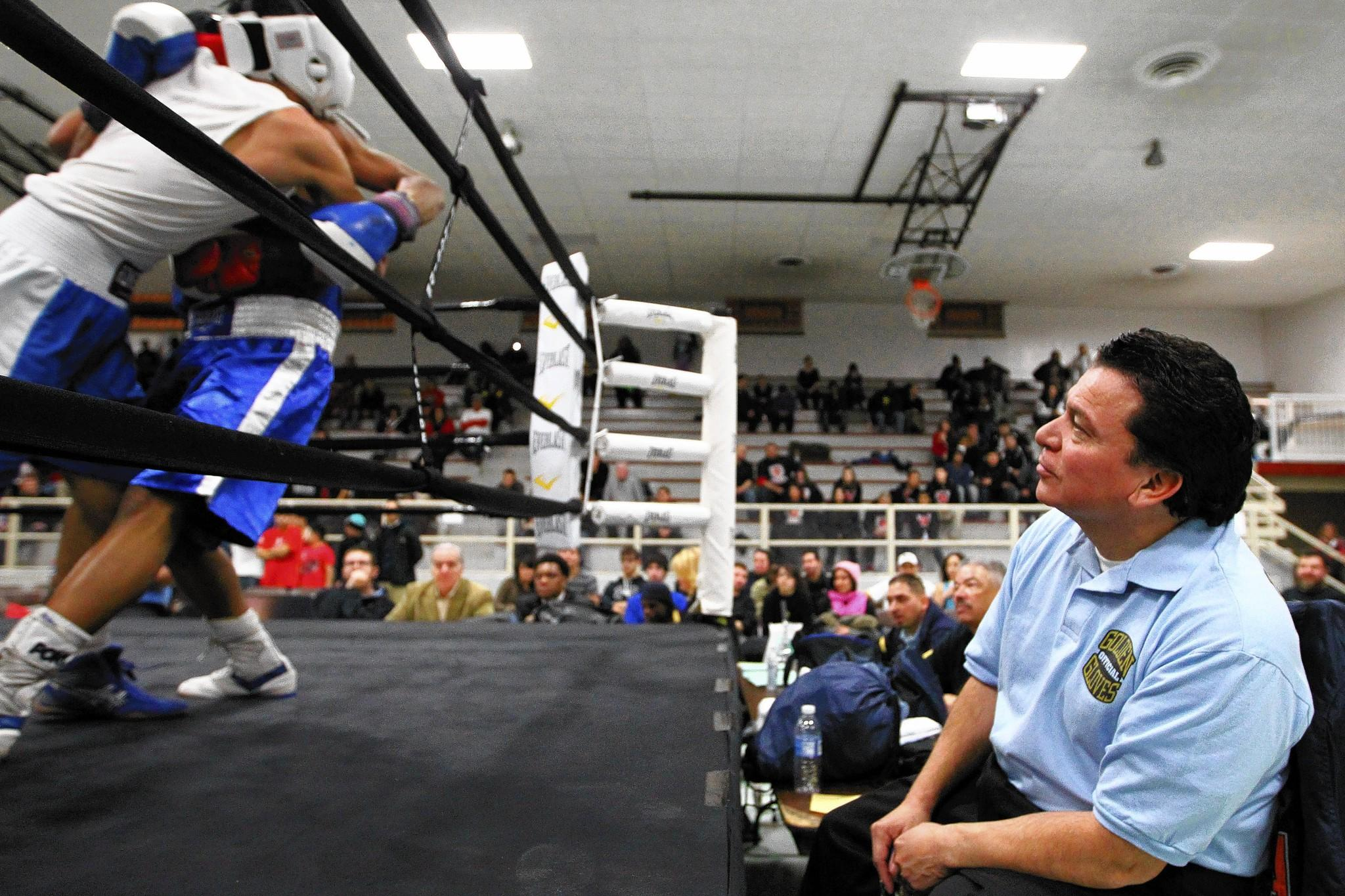 Joel Campuzano, right, watches a Golden Gloves boxing match in Cicero last year.