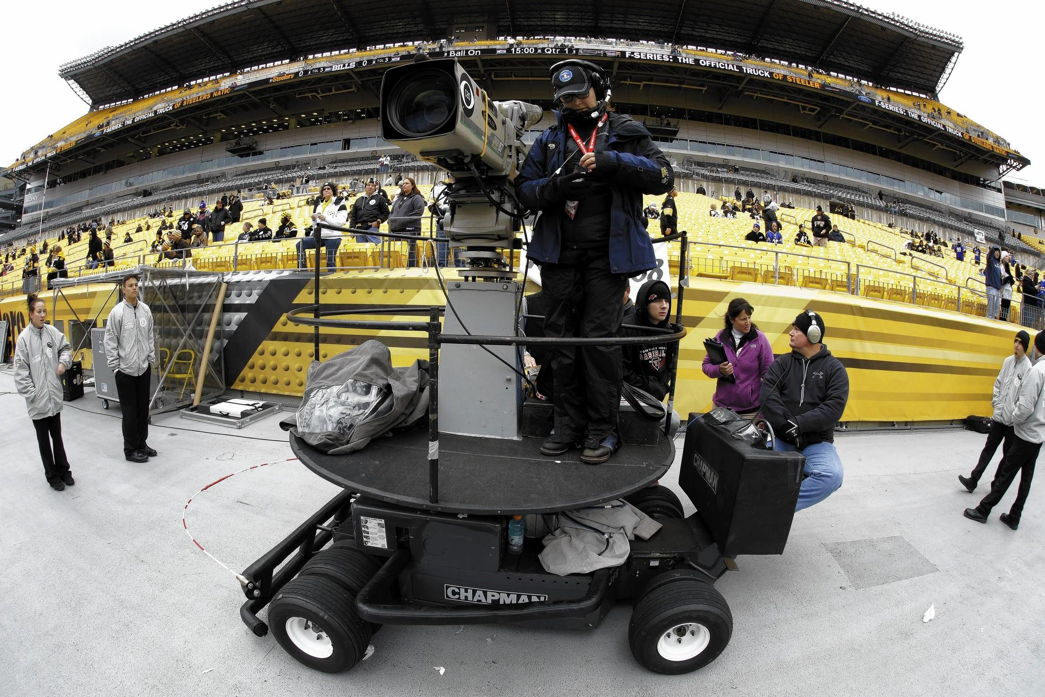 A CBS sideline camera operator prepares for an NFL football game between the Pittsburgh Steelers and the Buffalo Bills in Pittsburgh.