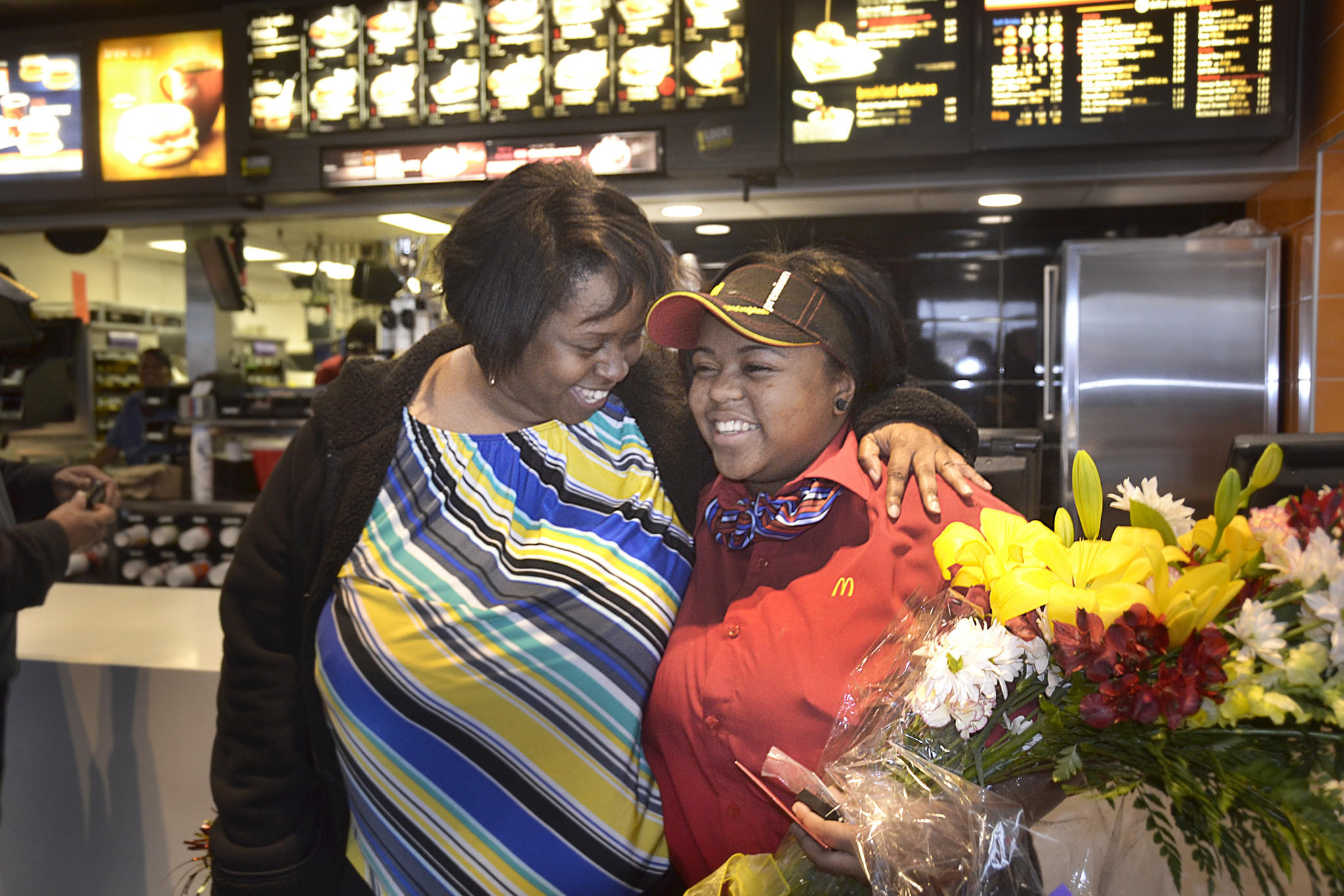 Brittany Jones (right) receives a hug from her mother, Shelia Jones (left), Wednesday morning after finding out she received one of 22 national McDonald?s Crew Member of the Year awards.