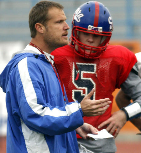 Gardena Serra Coach Scott Altenberg talks to quarterback Conner Preston duirng a practice.