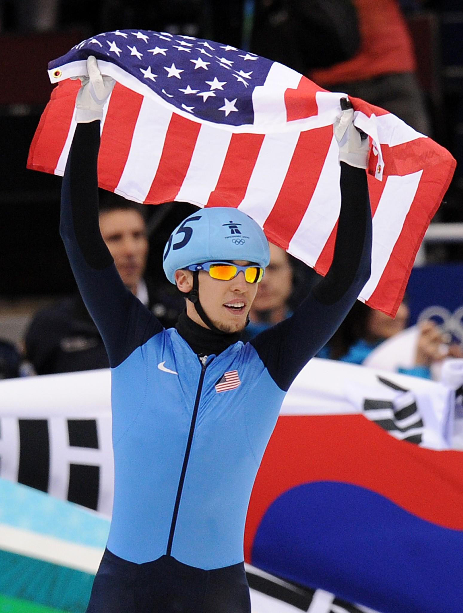 Jordan Malone celebrates with his country's flag at the end a race. (Yuri Kadobnov/Getty Photo)