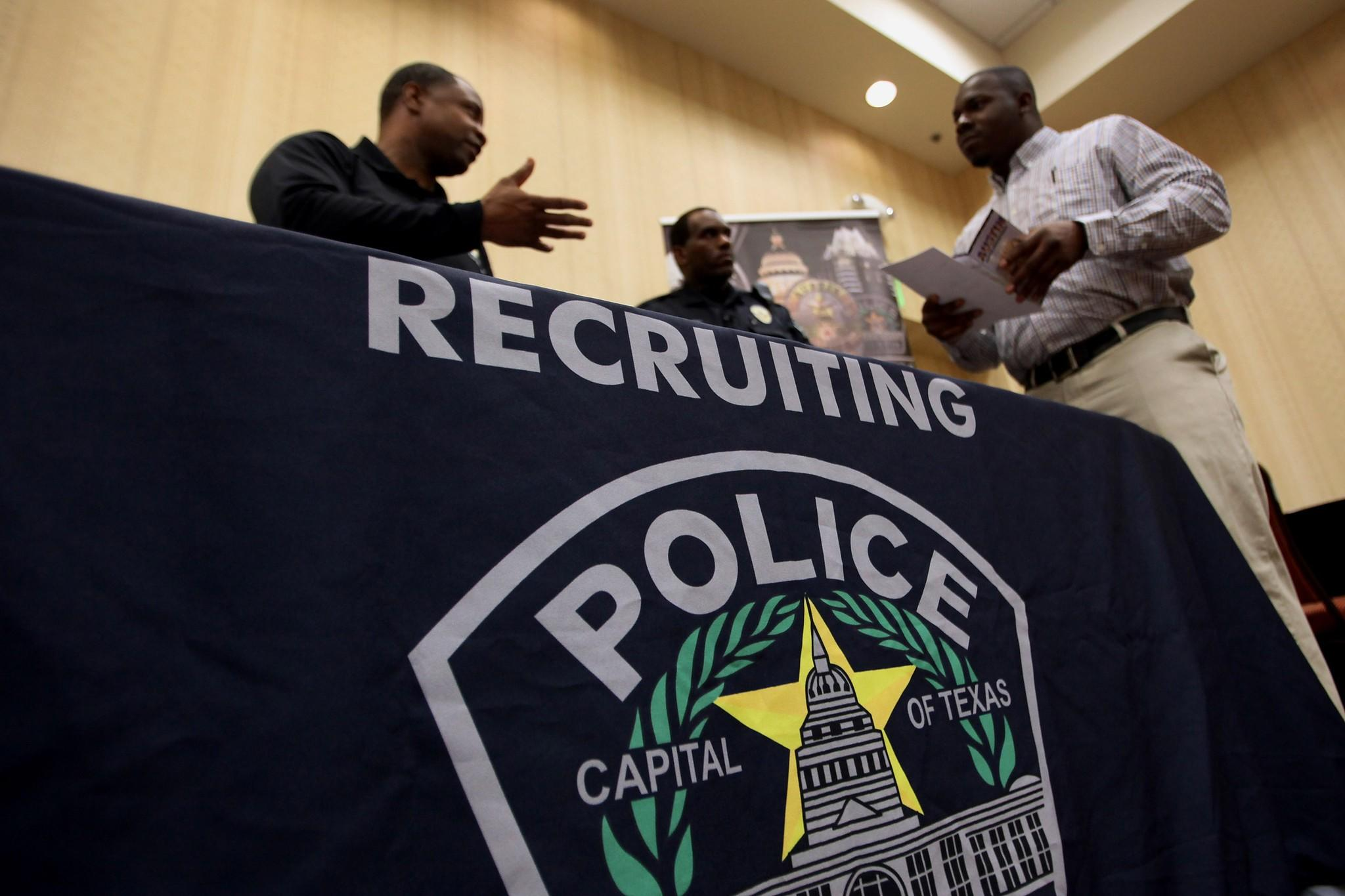 A job-seeker speaks to Austin, Texas, Police Department recruiters during a job fair hosted by JobExpo.com in Dallas.