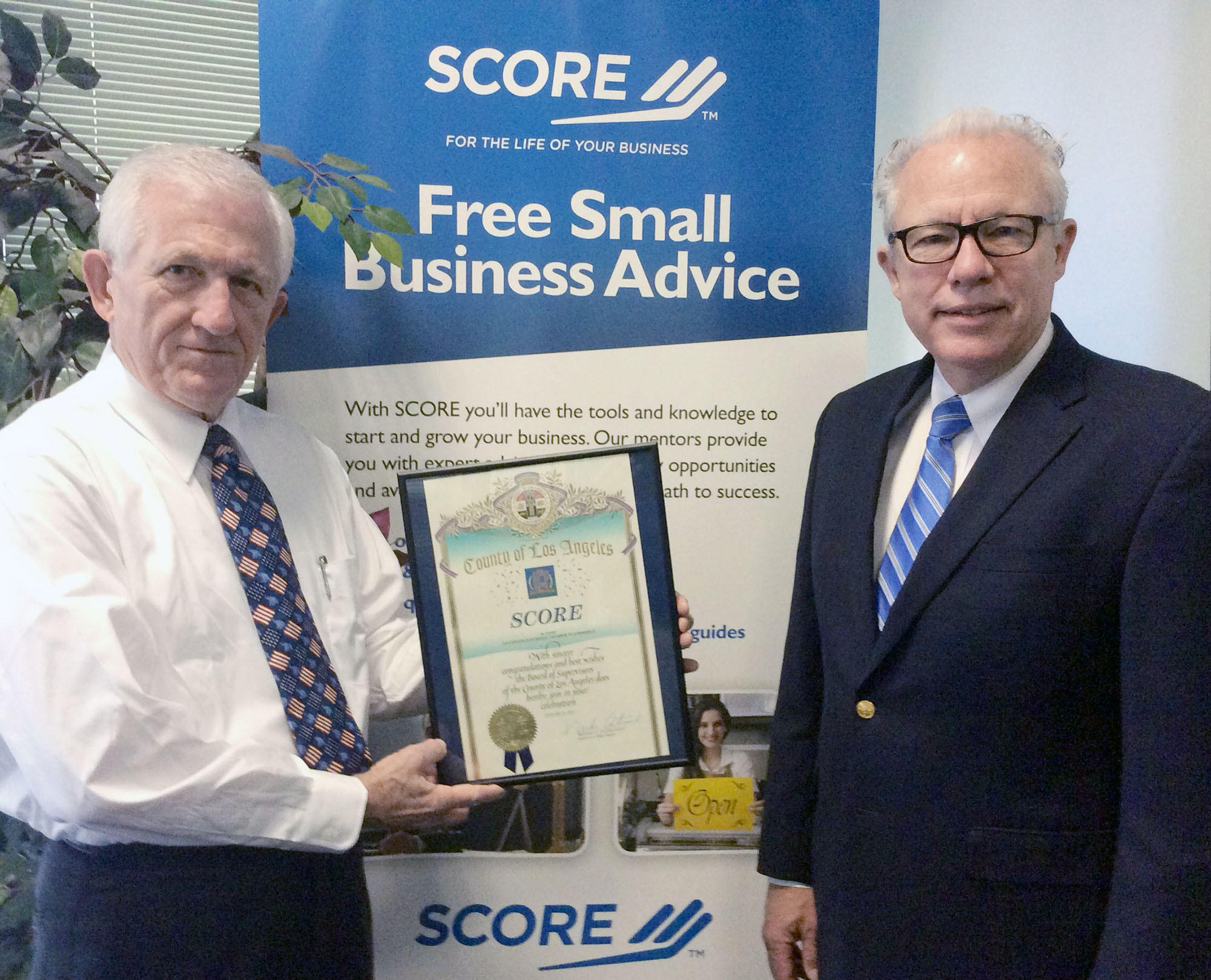 Dick Mader, left, and SCORE Chapter President Guy Langvardt accept recognition for the 50 years of services that SCORE of Greater Los Angeles has provided the local business community during a recent La Cañada Flintridge Chamber of Commerce and Community Assn. event.