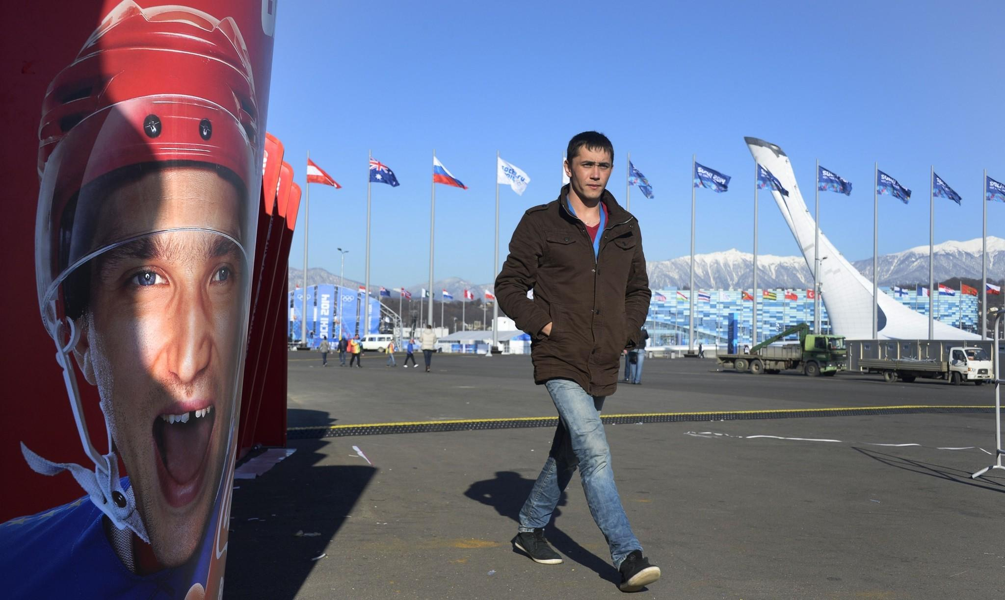 A man walks past a poster of Russian hockey star Alexander Ovechkin near the Olympic cauldron in the seaside cluster prior to the start of the 2014 Sochi Winter Olympics in Russia.