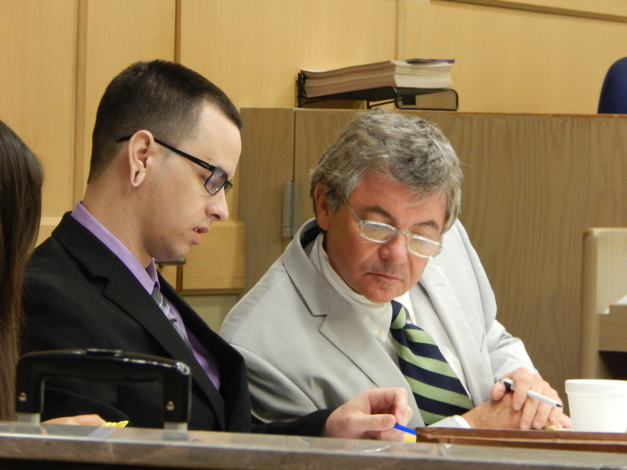 Andrew Nelson, left, reviews legal papers with defense lawyer James Lewis. Nelson is accused of his father's murder and his stepmother's attempted murder.