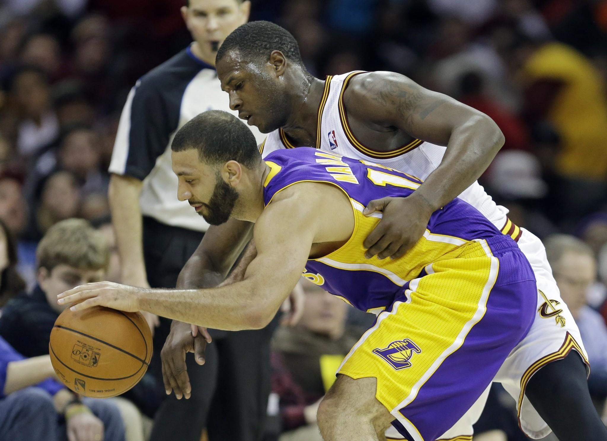 Kendall Marshall is defended by Cleveland's Dion Waiters during the fourth quarter of the Lakers' 119-108 win Wednesday over the Cavaliers.