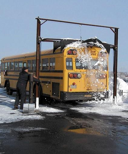 Parkland School District employee Duane Betz watches as the district's snow scraper clears the roof of a passing bus.