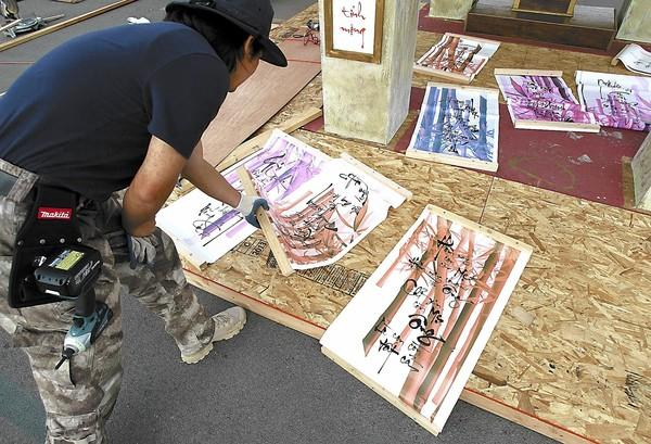 Richard Nguyen arranges panels of Vietnamese poems before adding them to the walls of a replica traditional temple as he prepares the site for upcoming Tet Festival of Southern California at the OC Fair & Event Center on Thursday.