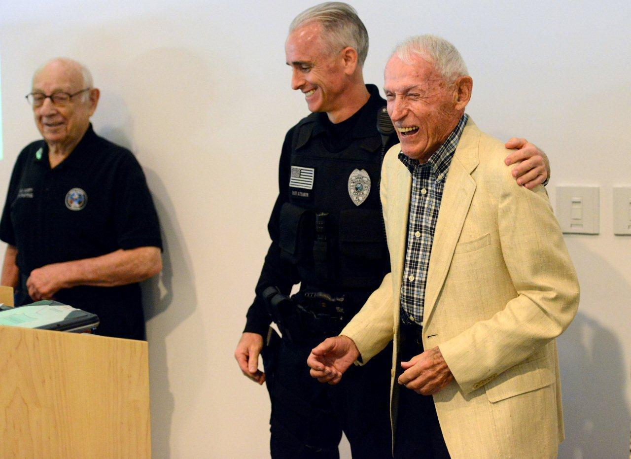 Boca Raton Police Chief Dan Alexander gives a hug to police volunteer Sam Iselin as fellow volunteer Al Scheinberg looks on from the left. The two volunteers were honored by the police department Friday with a party to celebrated Iselin's 100th birthday and Scheinberg's 96th birthday. Mark Randall, South Florida Sun Sentinel