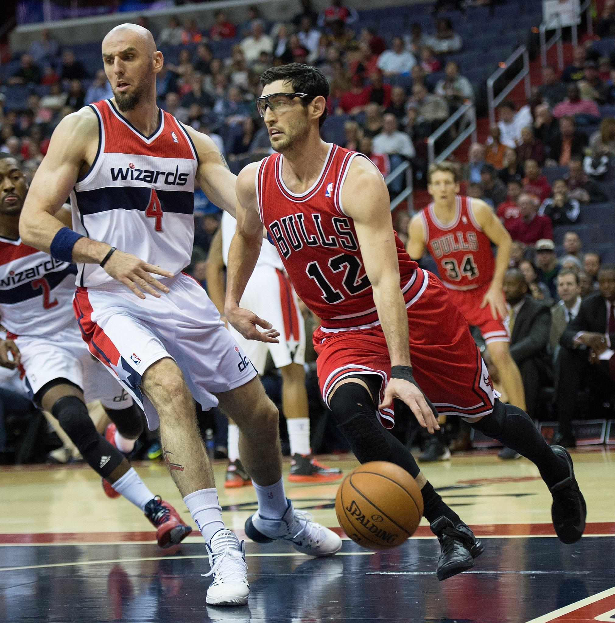 Chicago Bulls shooting guard Kirk Hinrich (12) drives under the basket pass Washington Wizards center Marcin Gortat (4) during the first half of their game played at the Verizon Center in Washington, Friday, Jan. 17, 2014.