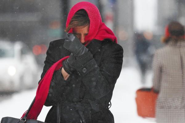 A woman bundles up Wednesday as she struggles against snow flurries in the Loop.