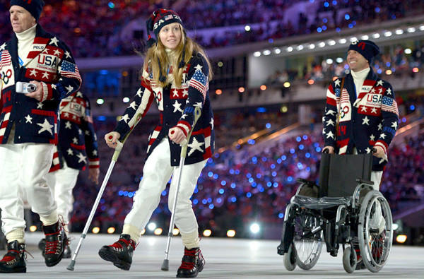 Heidi Kloser walks with crutches as she parades with her delegation during the ppening ceremony of the Sochi Winter Olympics on Friday at Fisht Olympic Stadium.