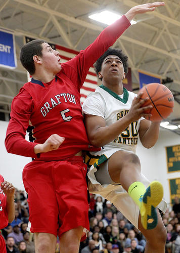 Deardre Kissoon of Bruton slips under Evan Sperling of Grafton for the first half layup Friday at Bruton.