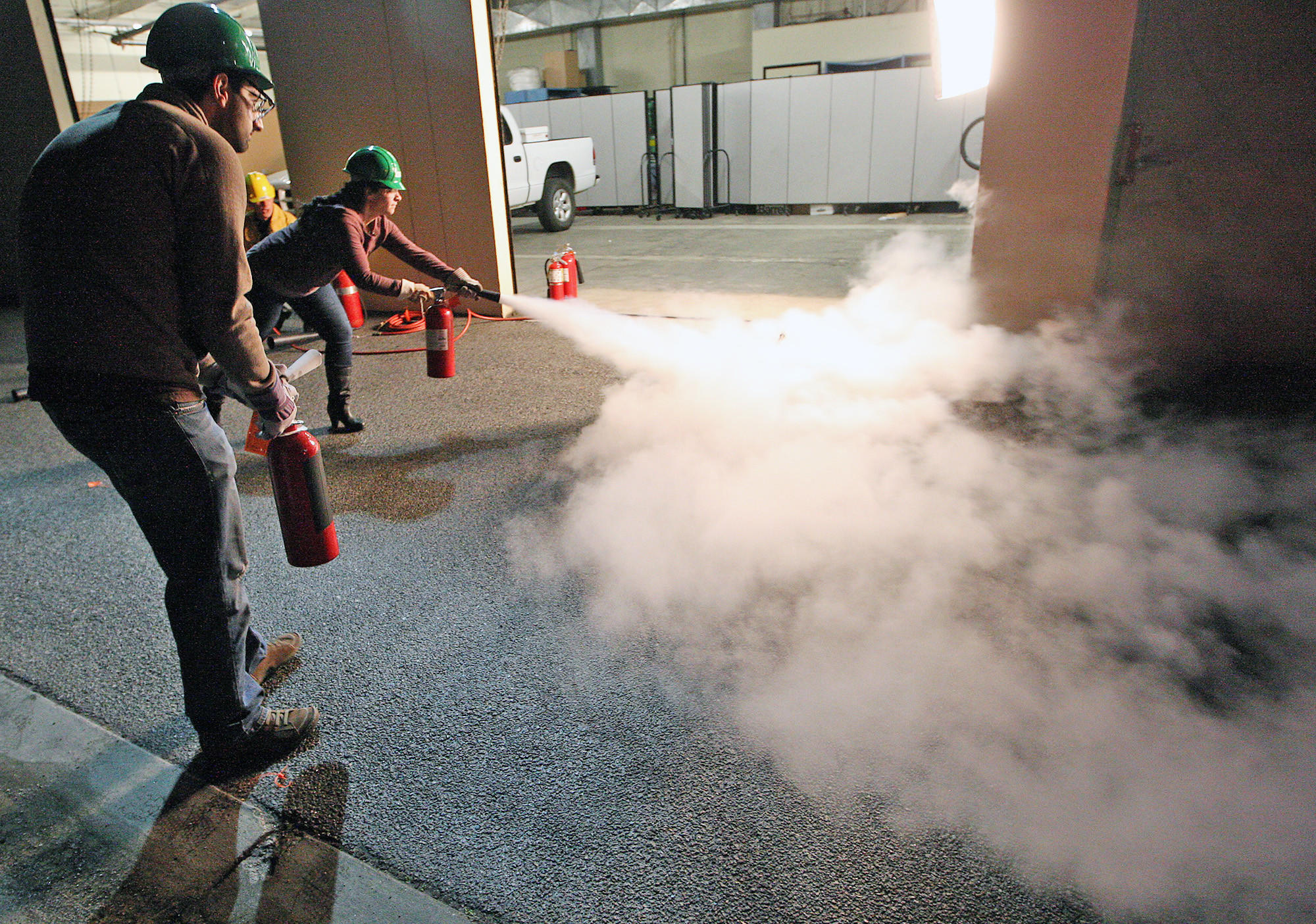 Glendale residents Reza Seraji and Ani Aharonian try their hand at putting out a fire with extinguishers during a CERT training program on Thursday, February 6, 2014.