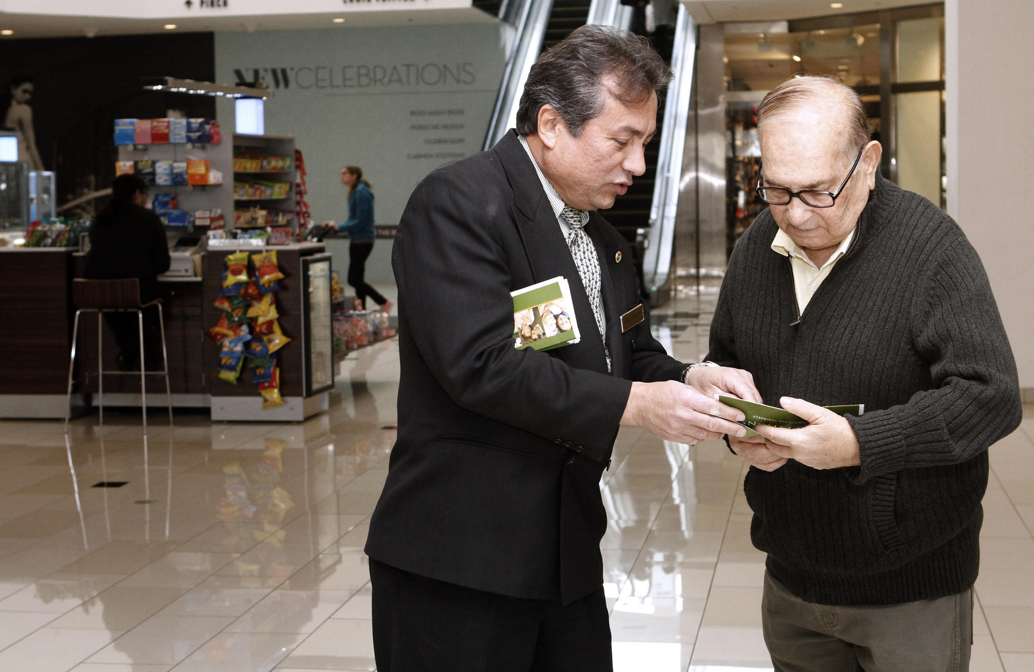 Forest Lawn Glendale advance planner Argenis Barreto, left, talks to Wadhu Bhojwani of Glendale about funeral planning at the FL kiosk at the Glendale Galleria on Friday, Feb. 7, 2014. The Forest Lawn kiosk has been at the mall next to Macy's since the beginning of 2014.