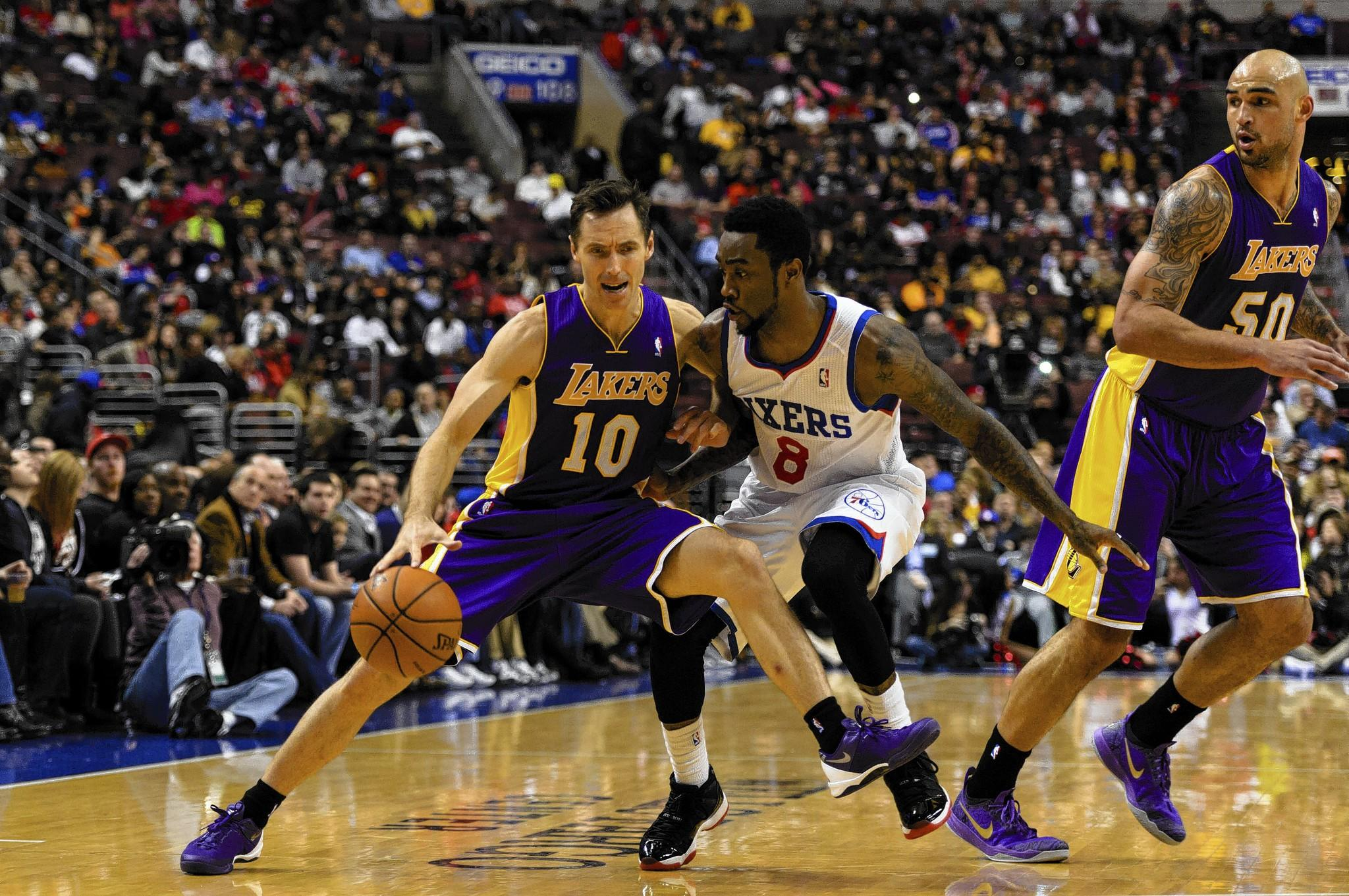 Feb 7, 2014; Philadelphia, PA, USA; Los Angeles Lakers guard Steve Nash (10) is defended by Philadelphia 76ers guard Tony Wroten (8) during the second quarter at the Wells Fargo Center.