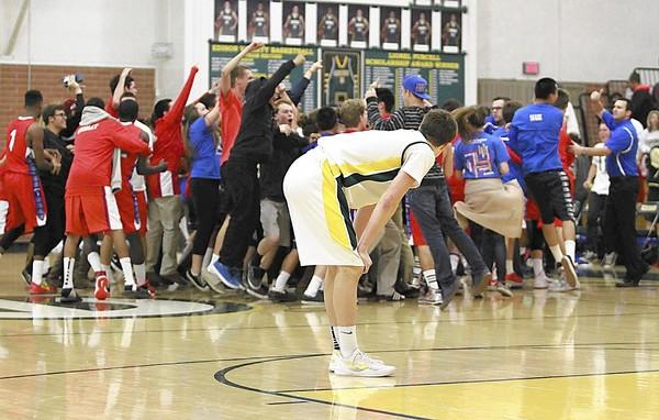 Edison's AJ Garrity can only watch as players, fans, and coaches from Los Alamitos storm the court after they held on to beat Edison, 52-51.